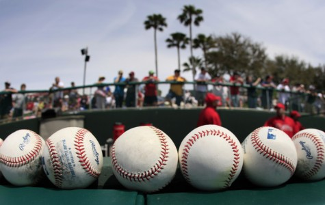 Fans stand above the Philadelphia Phillies bullpen before a spring training baseball game against the Atlanta Braves Wednesday, March 24, 2010 in Kissimmee, Fla. (AP Photo/Charlie Riedel)