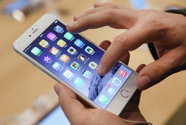 BERLIN, GERMANY - SEPTEMBER 19:  A shopper ltries out the new Apple iPhone 6 at the Apple Store on the first day of sales of the new phone in Germany on September 19, 2014 in Berlin, Germany. Hundreds of people had waited in a line that went around the block through the night in order to be among the first people to buy the new smartphone, which comes in two versions: the Apple iPhone 6 and the somewhat larger Apple iPhone 6 Plus.  (Photo by Sean Gallup/Getty Images)