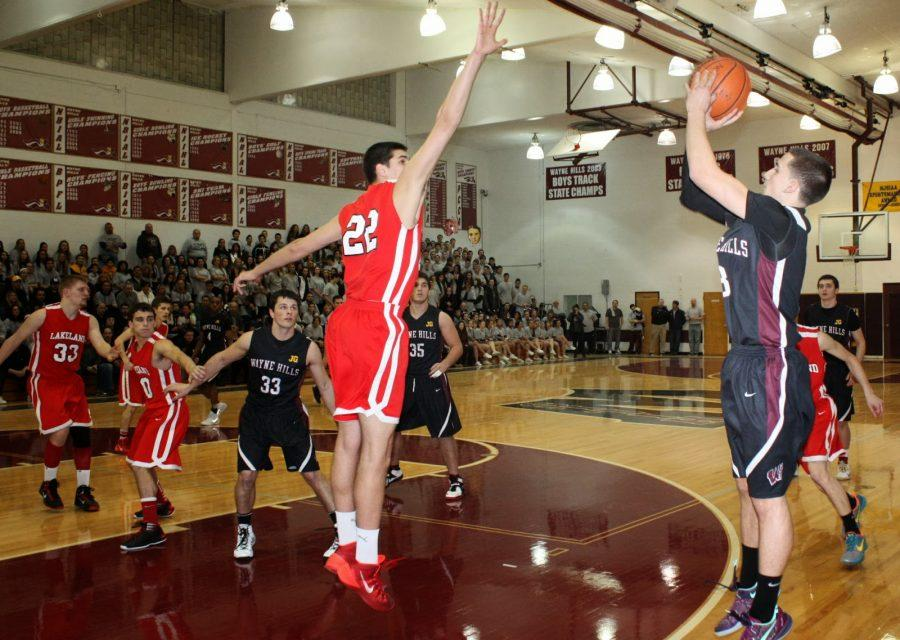 Justin Wills shoots a three pointer over a Lakeland defender
