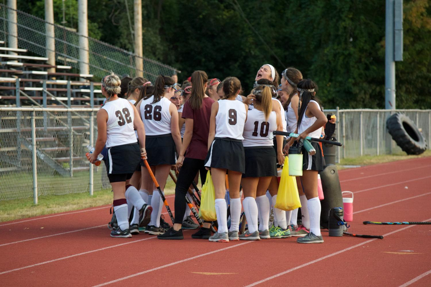 Some players from the WHHS Field Hockey Team huddling together.