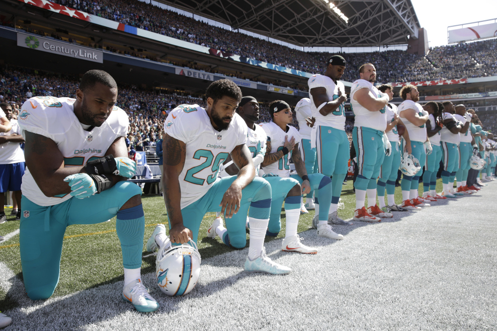 From left, Miami Dolphins' Jelani Jenkins, Arian Foster, Michael Thomas, and Kenny Stills, kneel during the singing of the national anthem before an NFL football game against the Seattle Seahawks.