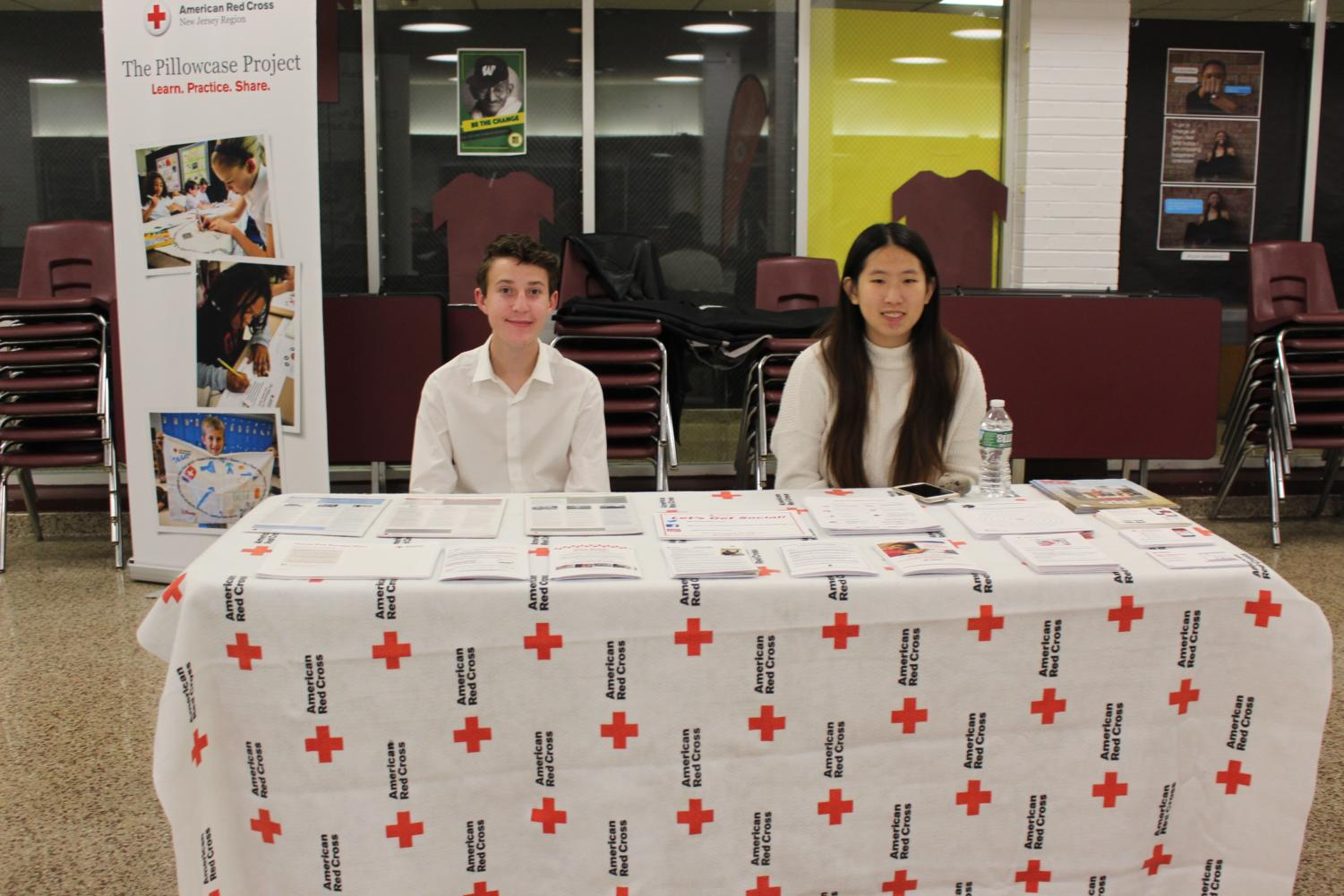 Freshman+Isaac+Gotian+and+senior+Jessi+Chen+manning+the+Red+Cross+informational+booth+at+the+concert.