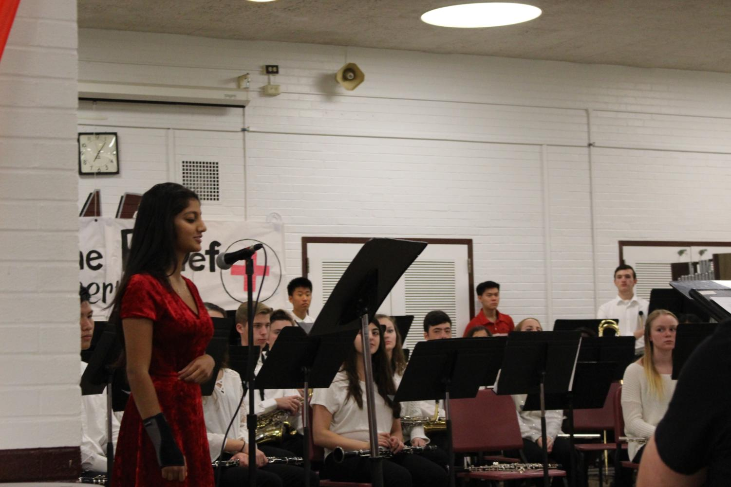 Pooja+Loka%2C+Vice+President+of+the+TRI-M+Music+Honors+Society%2C+introducing+the+TRI-M+choir+volunteers+and+their+performance+of+%22We+Are+The+World.%22+
