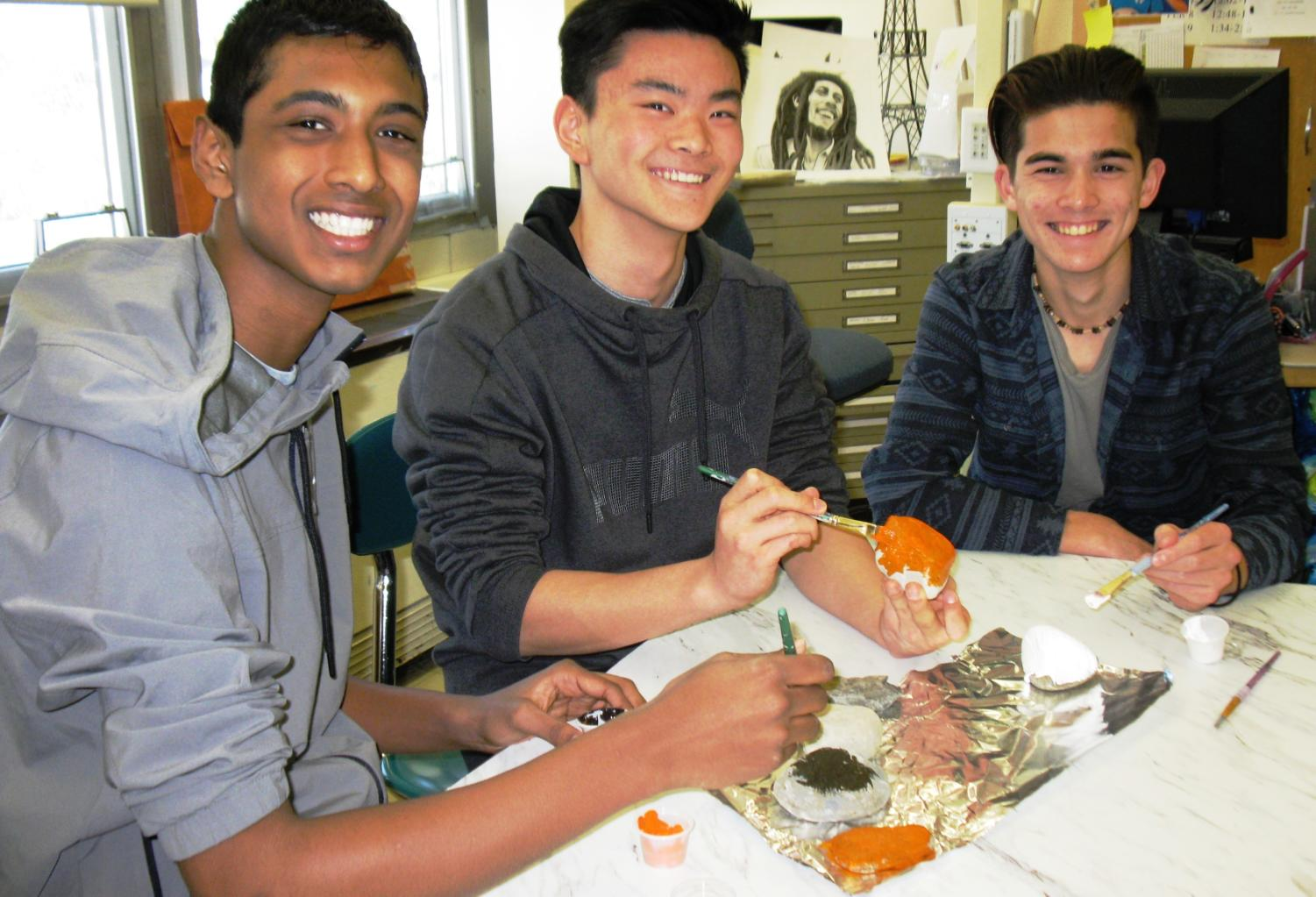 Tennis Club members, Kaushik Tallam, Shawm Joo, Jeff Angello paint rocks for the rock garden.