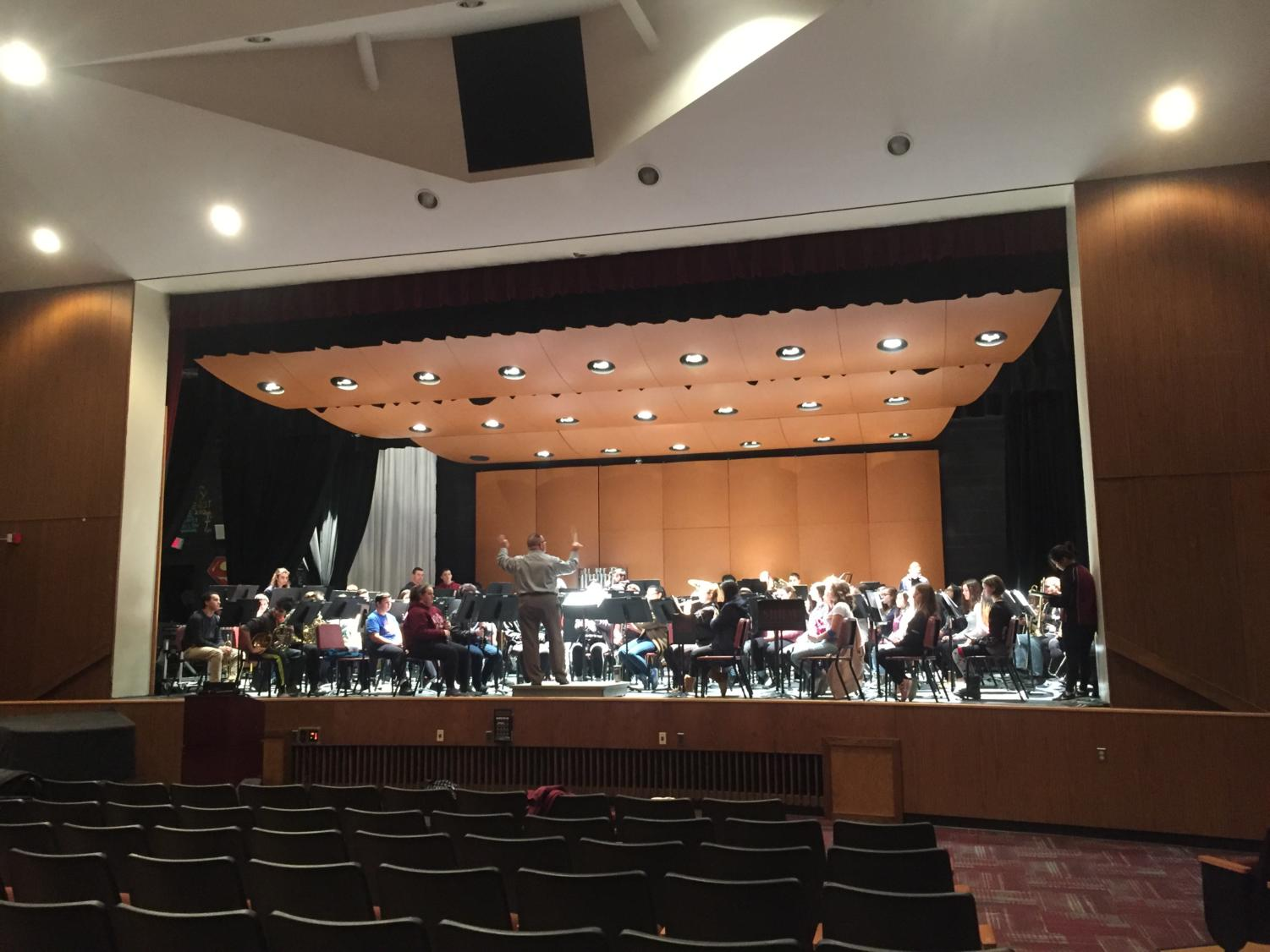 Band practicing before concert in auditorium