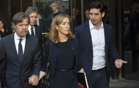 Felicity Huffman leaves Boston courtroom alongside her husband (left).
