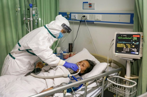 In this Thursday, Feb. 6, 2020, photo, a nurse feeds water to a patient in the isolation ward for 2019-nCoV patients at a hospital in Wuhan in central China's Hubei province. The number of confirmed cases of the new virus has risen again in China Saturday, Feb. 8, 2020, as the ruling Communist Party faced anger and recriminations from the public over the death of a doctor who was threatened by police after trying to sound the alarm about the disease over a month ago. (Chinatopix via AP)