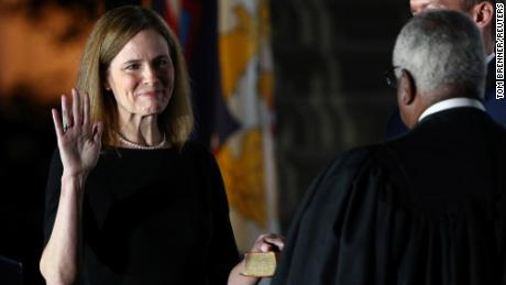Judge Amy Coney Barrett holds her hand on the Holy Bible as she is sworn in as an associate justice of the U.S. Supreme Court by Supreme Court Justice Clarence Thomas on the South Lawn of the White House in Washington, U.S., October 26, 2020.   REUTERS/Tom Brenner