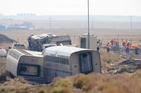 A train derailed in the middle of an empty field. Workers rescue trapped passengers.