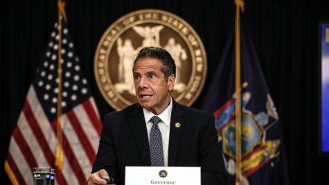 Andrew Cuomo sits at a table at a press conference announcing his resignation.