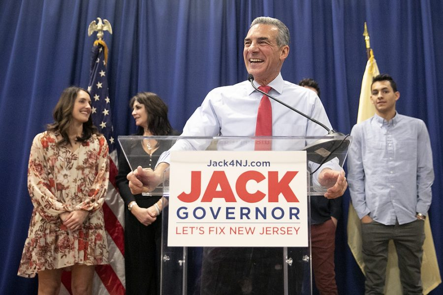 Republican Candidate Jack Ciattarelli stands at a podium smiling with his family standing behind him.